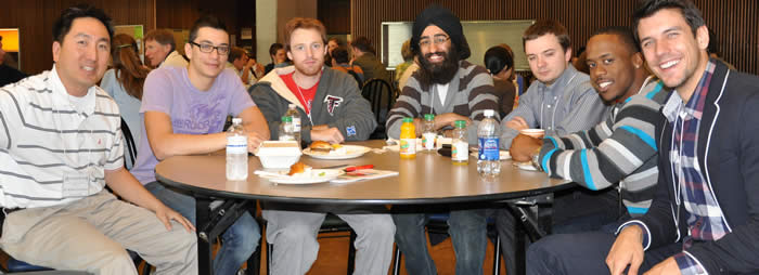 Robert Tsushima (far left) with attendees at a table in Stong Cafeteria