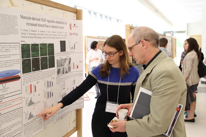 photo of presenter and attendee discussing poster in Life Sciences Building