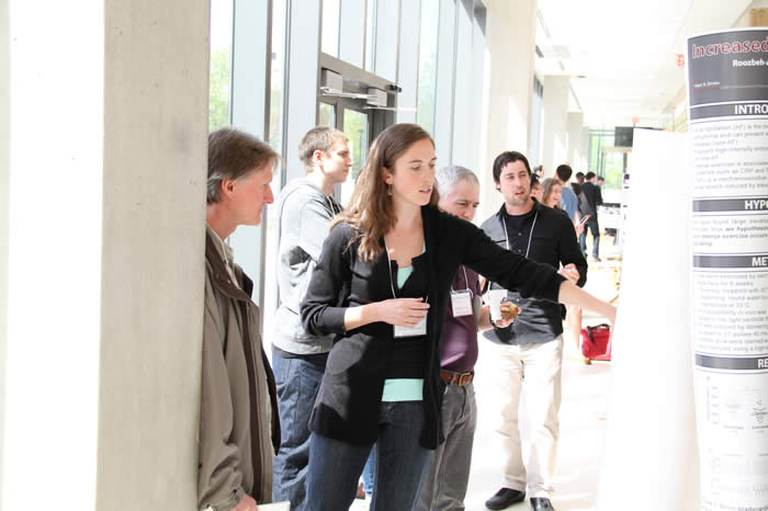 presenter engaged with attendee discussing poster in Life Sciences Building