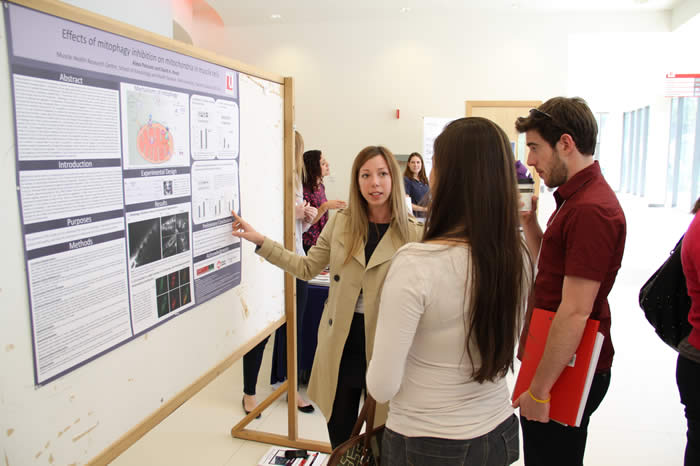 presenter discussing chart on poster with attendees in Life Sciences Building