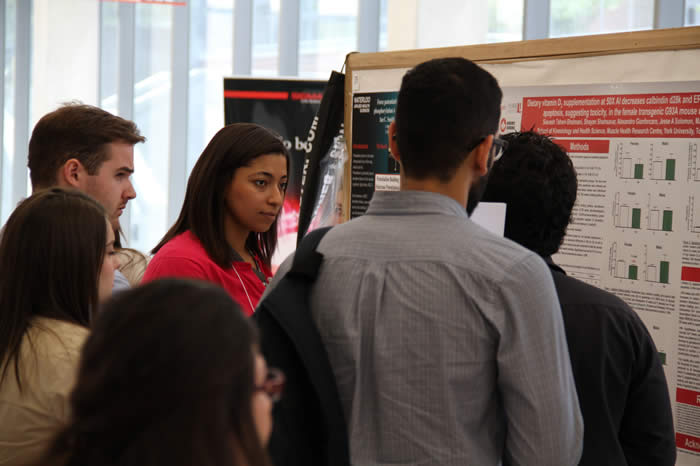 gathering of attendees at a poster in Life Sciences Building